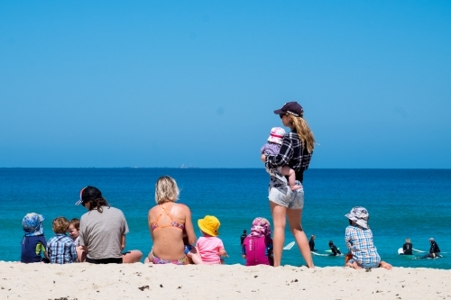 Mums and children on the beach looking out at the surfers on a summers day