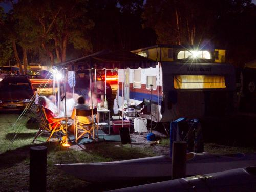 Campers relaxing at night outside a caravan