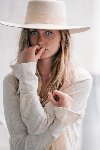 Natural tones and a young women wearing a hat.