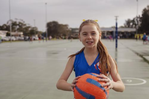 Netball girl holding ball pre game
