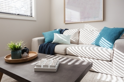 Neutral living room with textured fabrics and teal accents