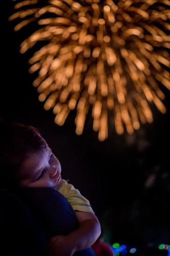 Cute mixed race baby boy cuddles his parent while new year's fireworks explode in background