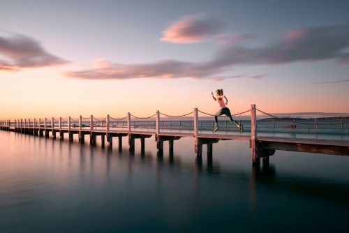 Woman running on pier at sunrise
