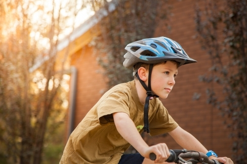 Nine year old boy riding his bicycle at home with helmet on