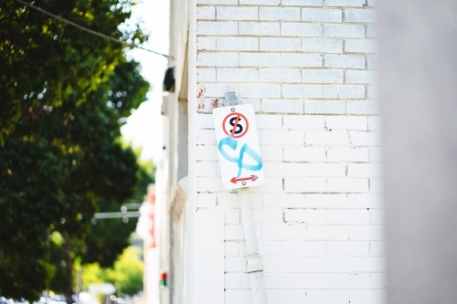 No standing sign with graffiti on white brick wall background