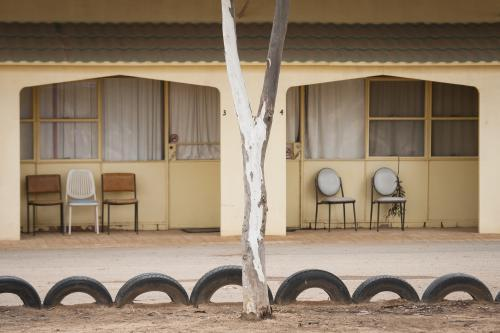Chairs outside a pale yellow motel on the Nullarbor
