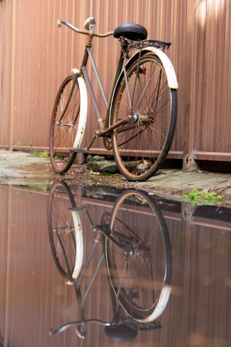 Old bicycle and reflection against corrugated iron fence