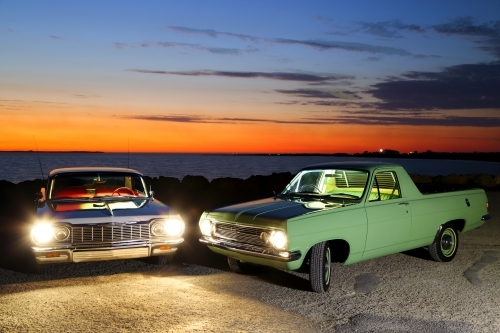 A light-painting of vintage 1967 Holden HR ute and 1964 Chevrolet Impala at dusk.