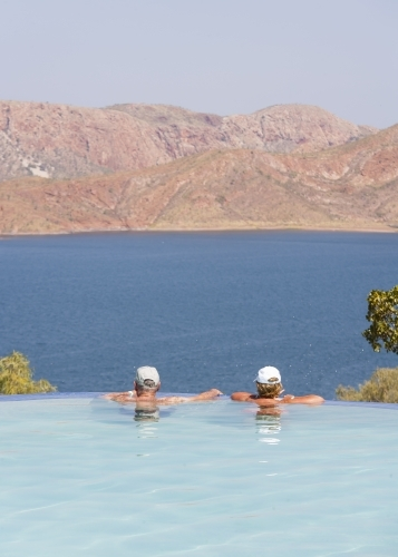Old couple relaxing in infinity pool