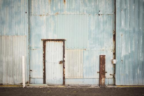 Old faded blue corrugated iron shed and door