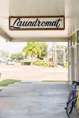 Old fashioned laundromat sign and empty footpath