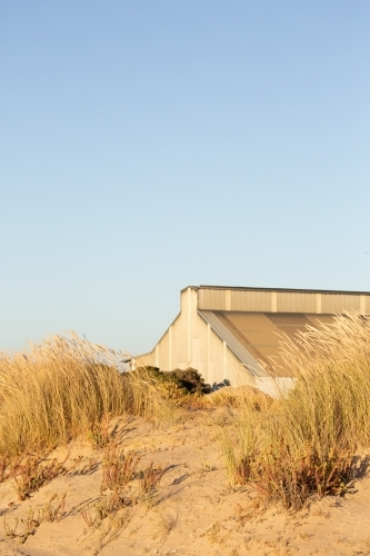 old industrial building at the port obscured in sand dunes