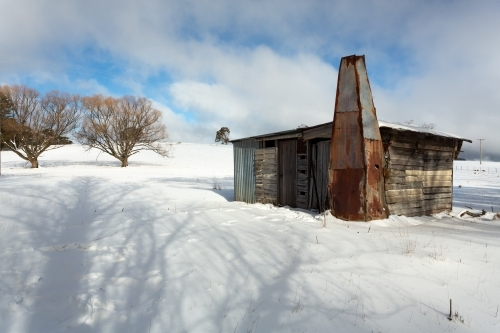 Old timber shack, shed or stable in a rural paddock with full coverage snowfall in winter. Blue sky