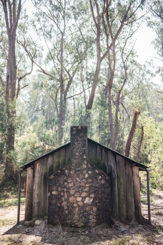 Old wooden shack with brick chimney in the bush