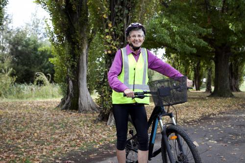 Older lady wearing high visibilty vest standing with bike