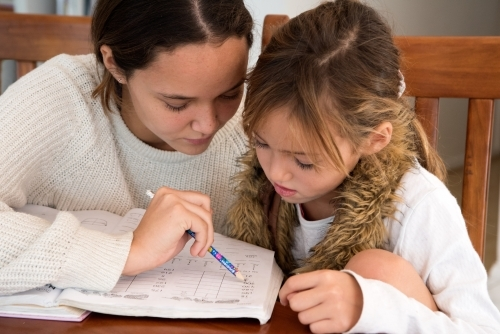 Older sister helping younger sister with school homework.