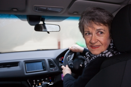 Older woman backing car out of driveway