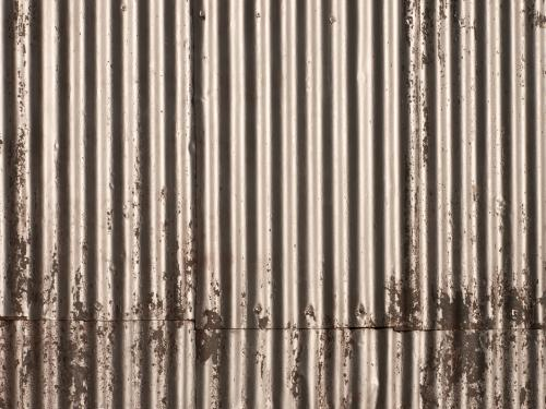 Corrugated iron wall with worn silver paint work