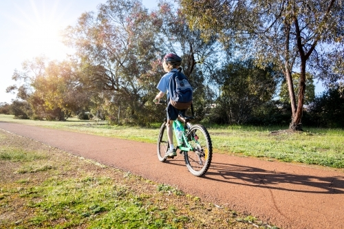 One child riding bike to school along path