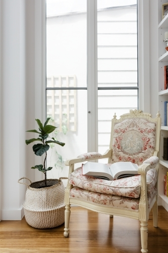 Open book on a comfortable vintage reading chair in a renovated home