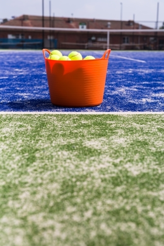 Orange basket of tennis balls on a blue and green tennis court