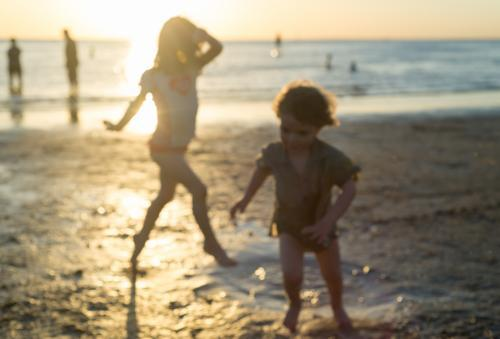 Out of focus young brother and sister playing on the beach at sunset
