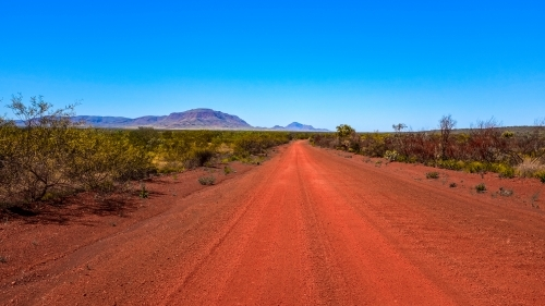 Outback red dirt road leading to mountains and blue sky