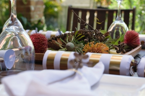 Outdoor Christmas table setting with native flowers and gold and white bon bon