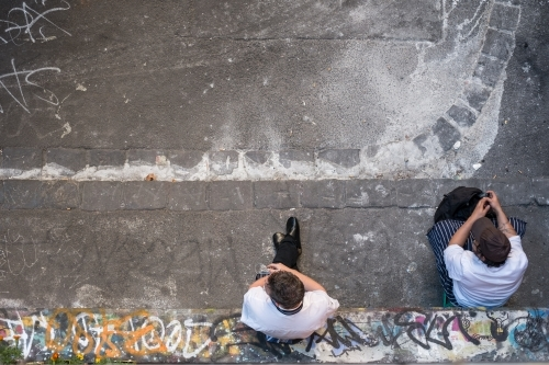 Overhead view of two men taking their break in a back alley