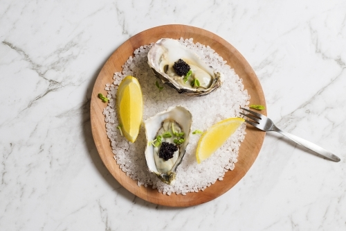 Oysters, topped with caviar on a plate