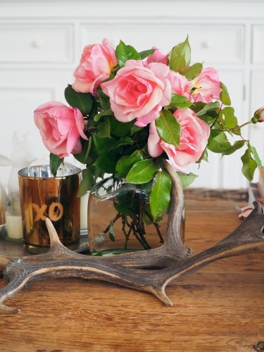 Styled coffee table with flowers, candle and antlers