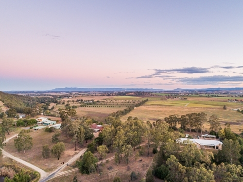 Pastel dusk sky over view of distant farm paddocks and cliff