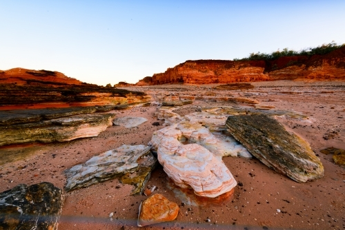 Patterned rocky beach bathed in pink sunset light