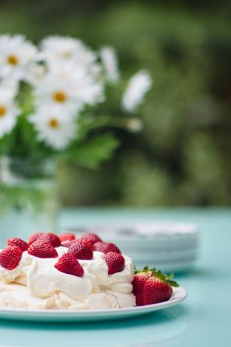 Pavlova topped with strawberries set out on a table outdoors in summer
