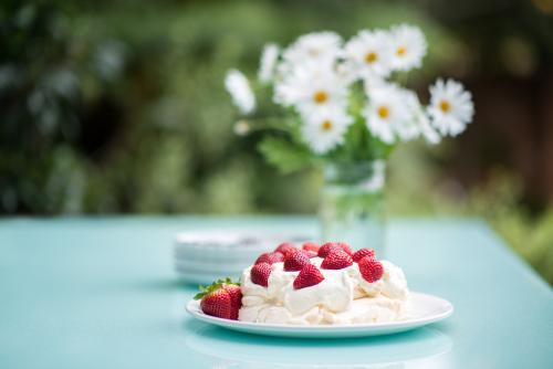 Pavlova with strawberries on an outdoor table in summer