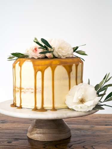 Caramel drip layer cake on cakestand with flowers