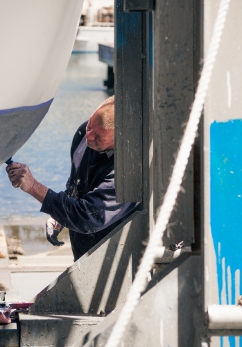 Man paints a boat in dry dock on the waters edge