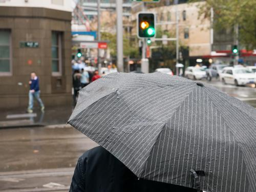 Pedestrians with umbrella wait at traffic lights on a rainy day