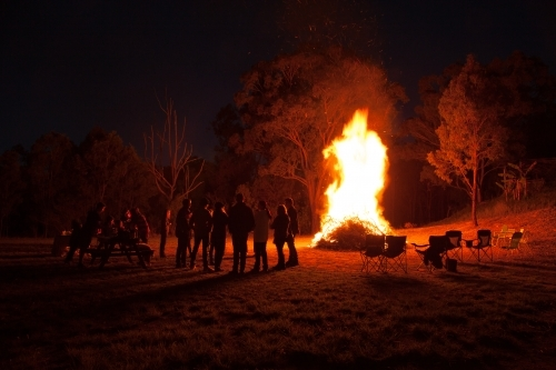 People and chairs around a blazing bonfire at night