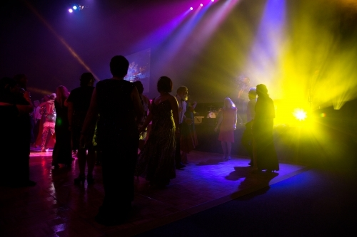 People dancing on dance floor at event with bright lights