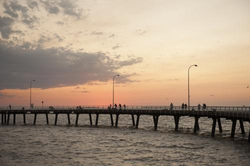 People fishing from Derby jetty at sunset