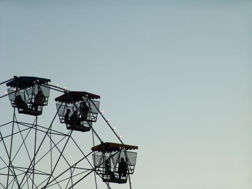People in a ferris wheel silhouetted against a blue sky