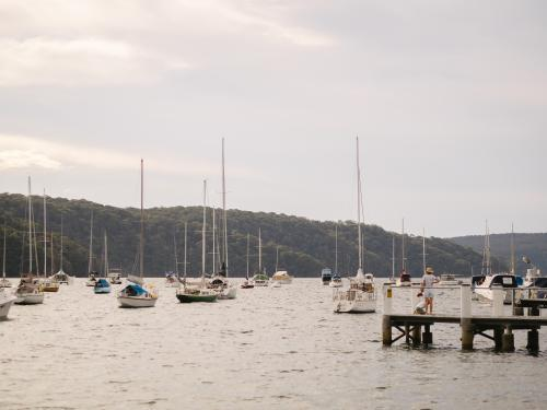 People on jetty and sailing boats with hills in the background