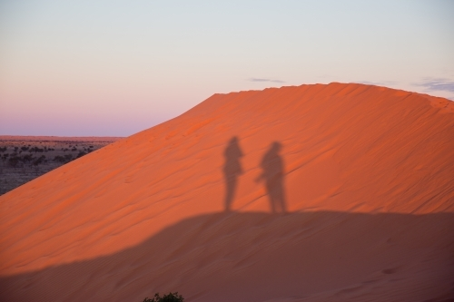 People shadows on red sand dune