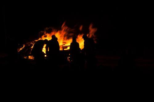 People standing around the bonfire talking