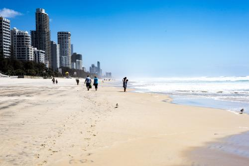 People walking along Gold Coast beach in summer with city in background