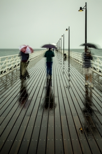 People walking on a pier with umbrellas on a rainy day.