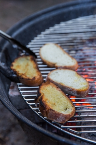 Person grilling thick slices of bread on hot coals on a bbq outside
