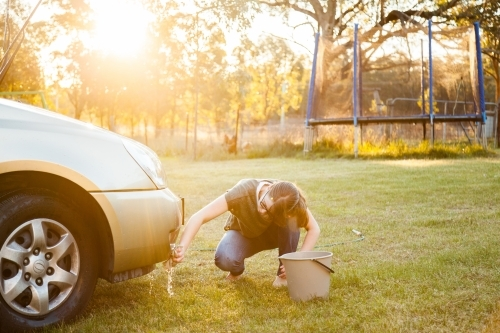 Person hand washing front of family car in backyard in natural light flare