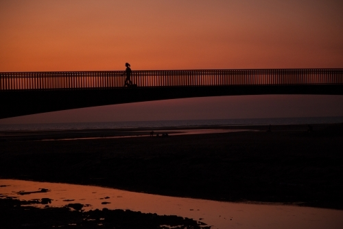 Person jogging across bridge at sunset